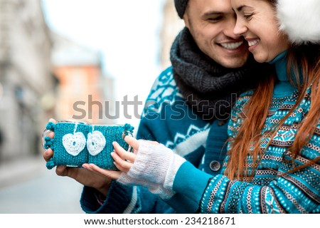 Young loving couple dressed in blue sweater sitting with knitted coffee cups on the bench at the old city in winter