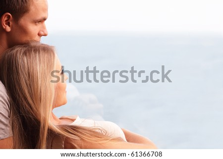 Young loving couple embracing and looking at a beautiful seaview in the window