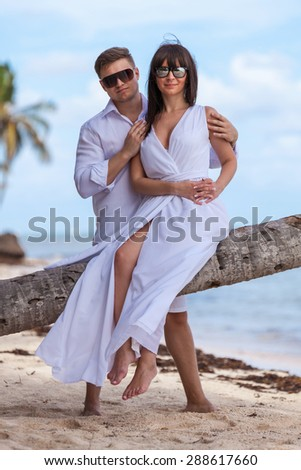 Young loving couple. Girl sitting on the palm tree.