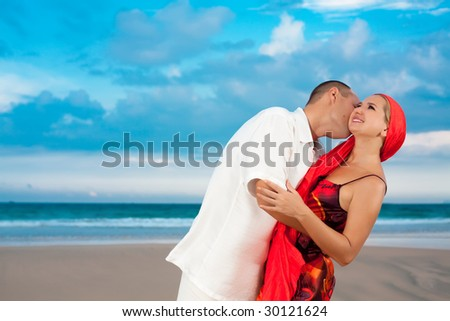 Young loving couple have a fun time near the ocean