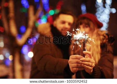 Young loving couple holding sparklers outdoors on winter evening #1033592452