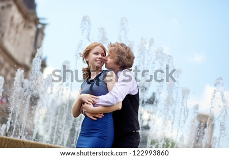 Young loving couple in Paris kissing near the fountain