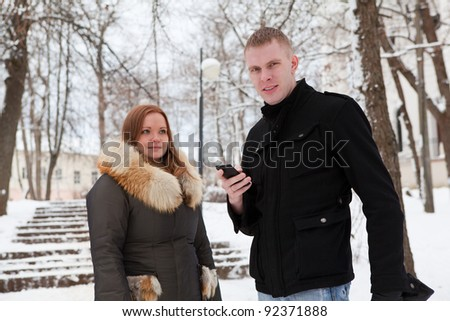 Young loving couple in winter time standing outdoor. Man holding a phone