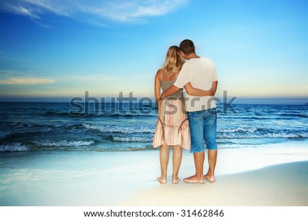 Young loving couple looking to the ocean