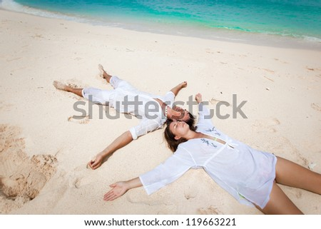 Young loving couple lying on caribbean beach, enjoying each other