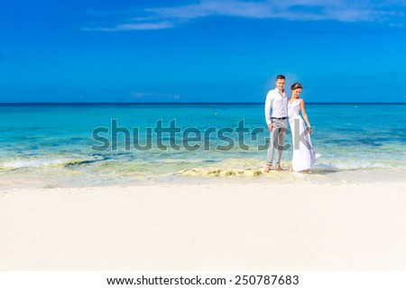 young loving couple on their wedding day, outdoor beach wedding in tropics