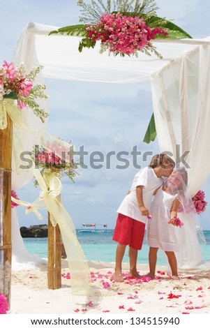 young loving couple on wedding day in beautiful wedding setup with flowers on tropical beach and sea background
