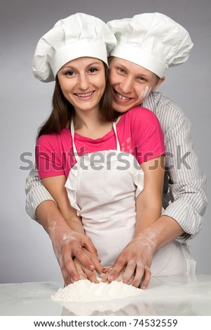 Young loving couple playing with dough. Over grey background #74532559