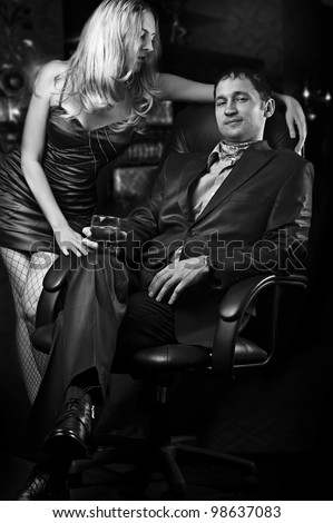 Young loving couple - sexy woman and rich man with glass of whiskey. Black and white