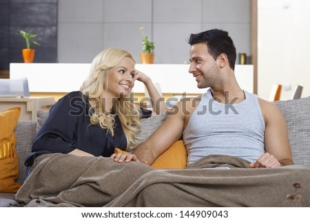 Young loving couple sitting on sofa at home, covered by blanket, smiling at each other with love.