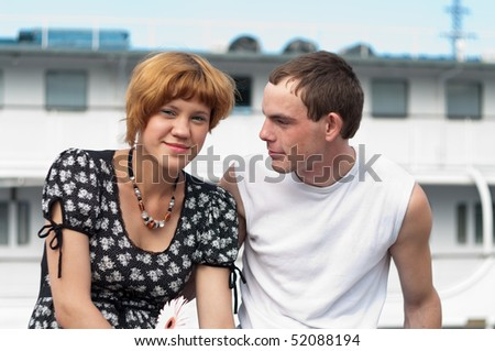 Young loving couple teens sitting. Two Caucasian people. Teenagers: girl and boy embracing one another