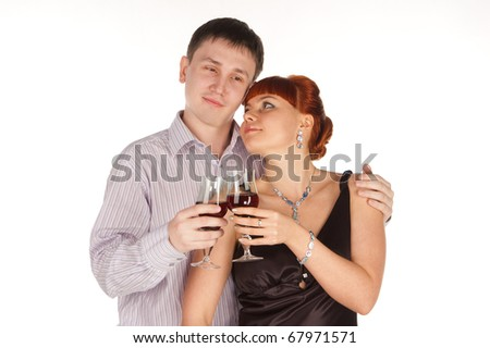 Young loving couple with red wine glasses in hands. A white background. Isolated.