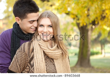 young loving couple, young man whispers his girlfriend