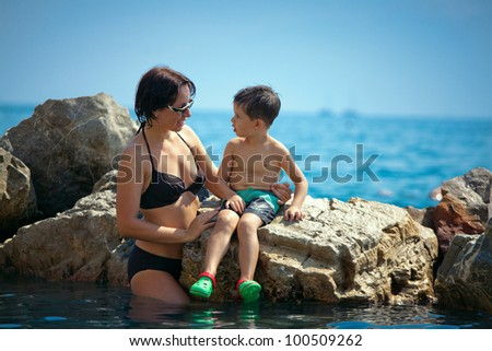 Young loving mother talking with her toddler son on a rocky seashore