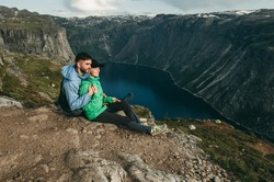 Young loving romantic couple sitting and hugging near blue lake in Norway near rocky mountain fjords in summer. Woman and man in green and blue sports hiking jackets. Traveling Europe