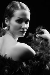 young luxury woman in retro vintage style on black background looking at camera, monochrome