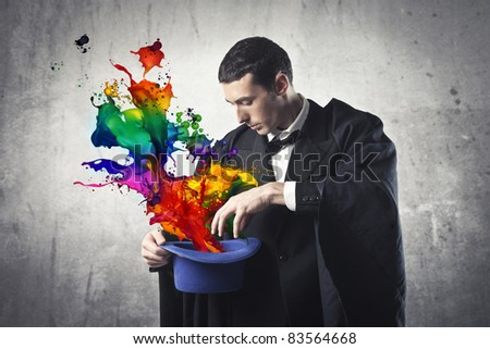 Young magician extracting colored paint from a cylinder hat