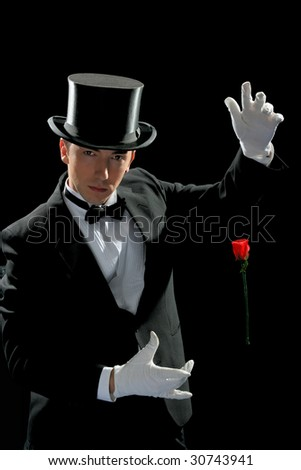 Young magician in tuxedo and high hat performing with flying red rose