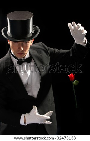 young magician performing red rose on black background