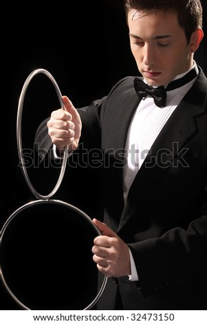 young magician with silver metal rings on black background