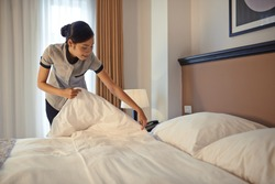 Young maid arranging blanket on bed in hotel room