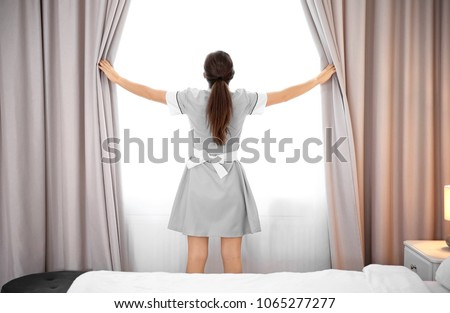 Young maid opening curtains in hotel room Сток-фото ©