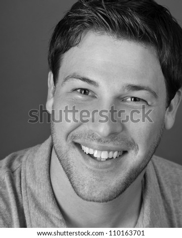 young male actor making emotional facial expression in front of camera - stock photo