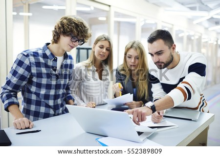 Young male and female classmates testing their IT project application correcting mistakes and finding bugs in program via modern laptop computer and wireless connection to internet working in library