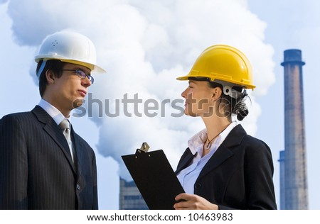 Young male and female managers working together in an industrial situation with