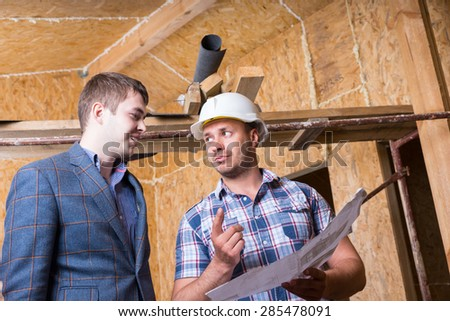 Young Male Architect and Construction Worker Foreman Consulting Building Plans Inside Unfinished House with Exposed Particle Plywood Boards