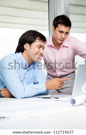 Young male architect pointing at laptop screen while colleague standing beside.