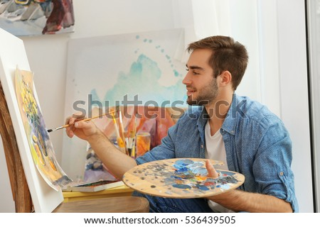 Young male artist painting picture in studio #536439505