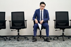 young male asian job seeker sitting in chair appears to be frustrated and defeated