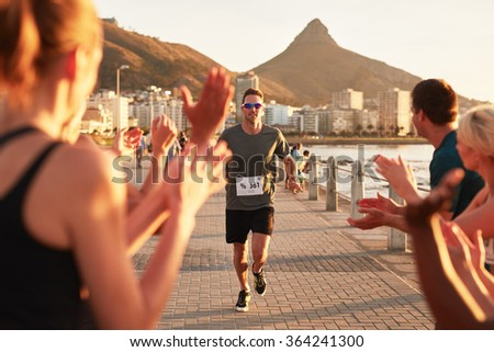 Young male athlete being applauded by supporters as he reaches the finishing line of a running race. Young people encouraging race runners outdoors in the city.