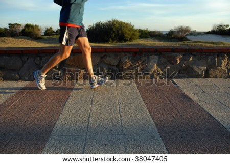 Young male athlete jogging at the promenade. Legs in motion. A quiet beach with sand dunes on the background