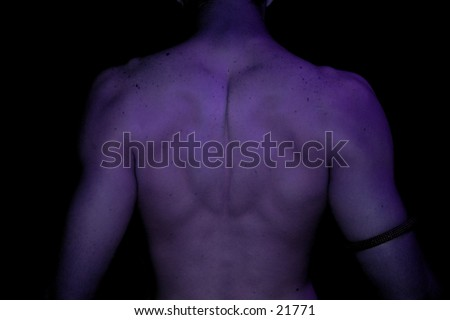 young male back showing muscles in purple light