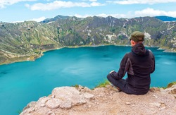 Young male backpacker enjoying the landscape of the Quilotoa volcanic lake on the highest peak at 3930m altitude along the Quilotoa Loop hike, Quito, Ecuador.