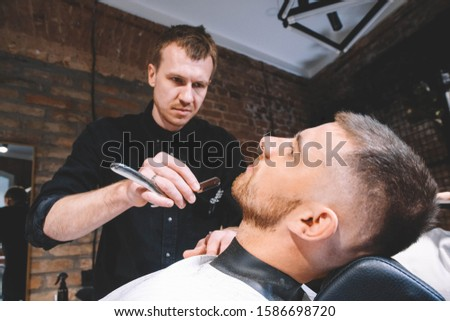 Young male barber makes a haircut beard client with vintage straight razor. Shaving process of beards in Barbershop
