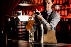 young male bartender accurate pouring drink from jigger into steel glass of shaker on bar counter