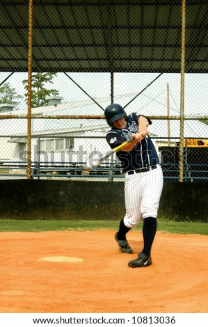 Young male baseball player connects with the pitch.  Ball line drives toward pitcher.