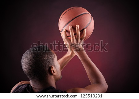 Young male basketball player against black background