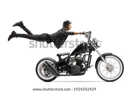 Young male biker riding a chopper and flying isolated on white background Stock photo ©