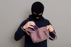 Young male burglar steals woman's handbag, opens bag and looking inside, pulls out wallet, wearing black sweater and burglar mask, robber posing isolated over gray background.