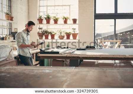 Young male business owner standing in his studio workshop checking figures and stock on his clipboard on a sunny afternoon
