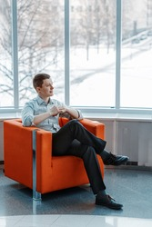 Young male businessman is sitting in an orange chair. He smiles.