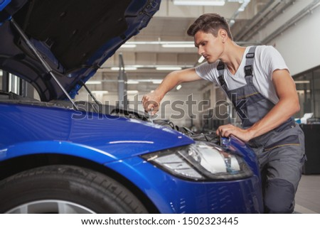 Young male car service worker repairing engine of an automobile at the garage, copy space. Auto technician working under the hood of a car #1502323445