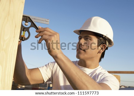 Young male carpenter with spirit level working at construction site