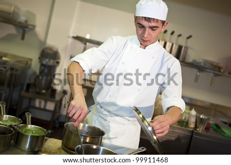 Young male chef cooking meal at the stove stirring food in a pan - stock photo