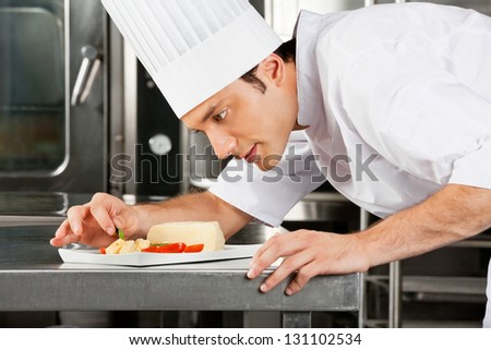 Young male chef garnishing dish in commercial kitchen
