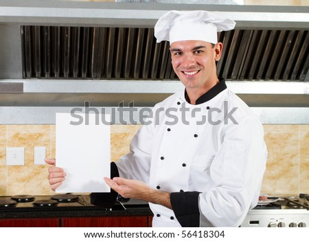 young male chef holding white board in kitchen